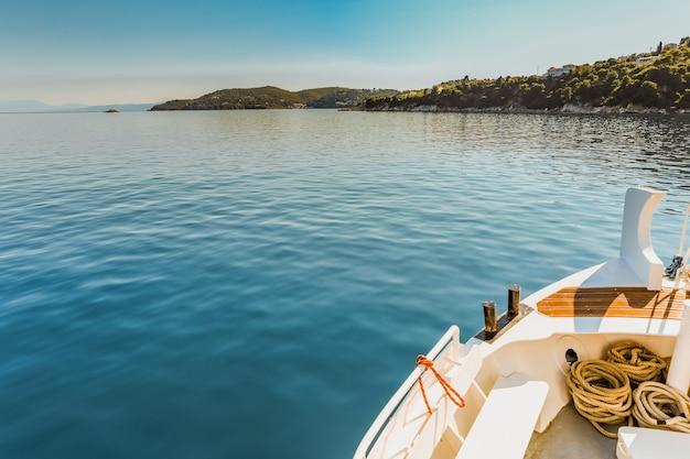 澄んだ青い空の下で緑の島の近くの水の体に白いカヌーのワイドショット