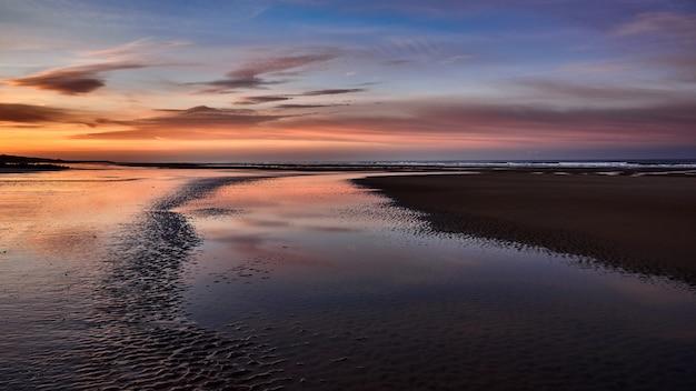 Широкий снимок красивого побережья моря с удивительным облачным небом во время золотого часа