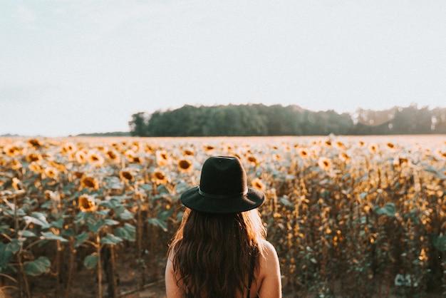 大きな美しいひまわり畑の前に立っている若い女性