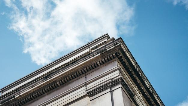 白い雲と澄んだ青い空の下で建築物のローアングルショット