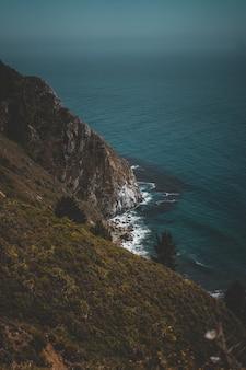Вертикальная съемка холмистого зеленого побережья и голубого океана с камнями