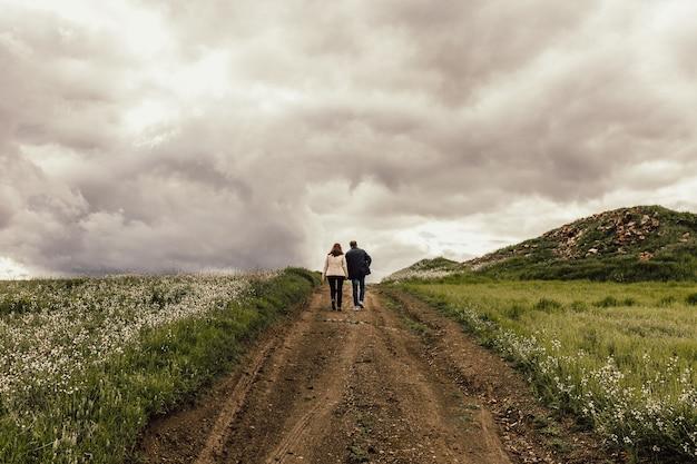 霧の空の下で花と谷の小道を歩いている男性と女性のショット