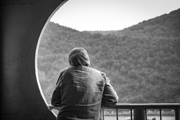 Женщина в хиджабе стоит на балконе в черно-белом