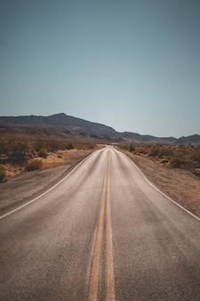 バックグラウンドで美しい丘と空の狭い砂漠の道