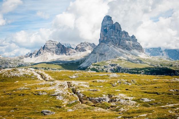 昼間の曇りの青い空の下の広いフィールドの芝生の上の岩の形成