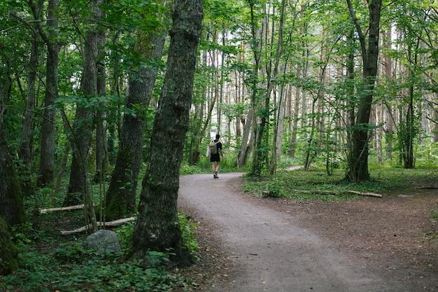 森の真ん中にある小道を歩いているバックパックを持つ男性