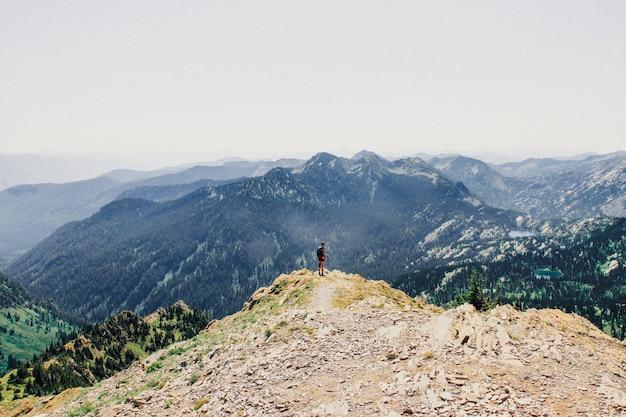 Красивый снимок человека, стоящего на краю обрыва с лесистыми горами
