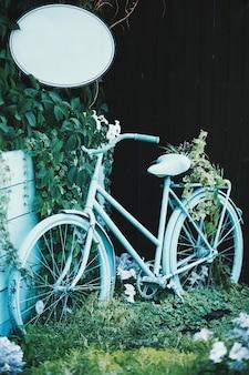 Голубой велосипед возле зеленых растений