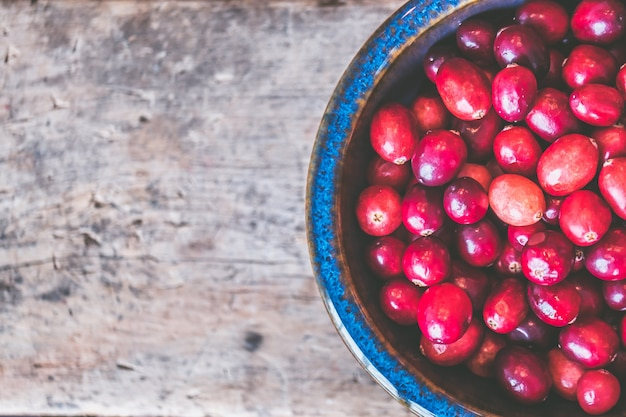 Макрофотография выстрел из красных кофейных зерен на деревянной серой поверхности