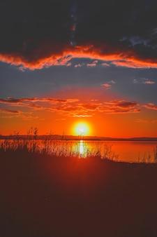 Красивый закат на озере с зеленью на побережье и удивительным облачным небом
