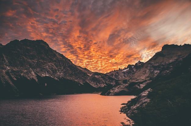 素晴らしい雲と湖のほとりにある山の夕日の美しいショット