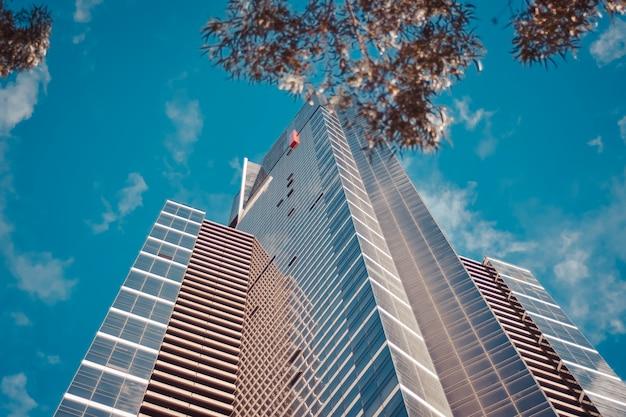 青い曇り空と背の高いビジネスビルのローアングルショット