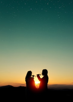 Красивая съемка силуэтов пары выпивая вино на заходе солнца