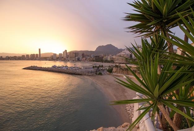 Воздушная съемка пляжа рядом с городом во время заката