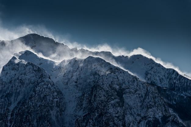 Красивые высокие снежные и туманные горы со снегом, уносимым ветром