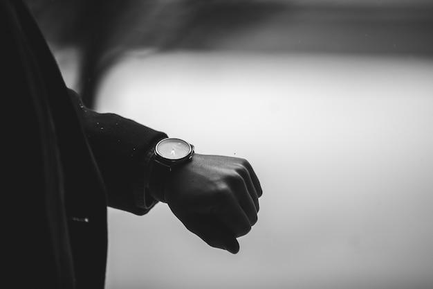 腕時計を着ている人のグレースケールのクローズアップショット