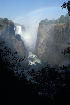 虹と青空の下で背の高い丘から流れる滝の垂直ショット