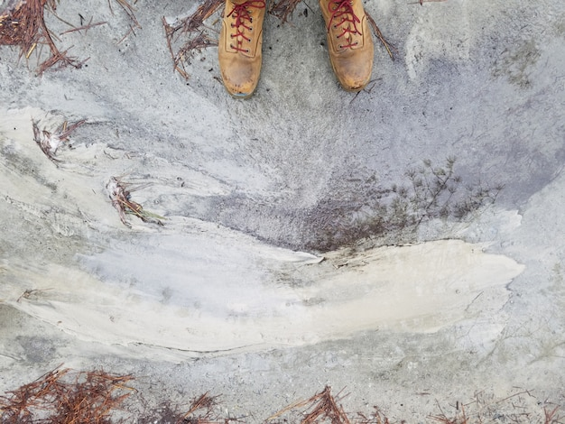 風化したコンクリートの地面に立っている茶色の革の靴で人の足