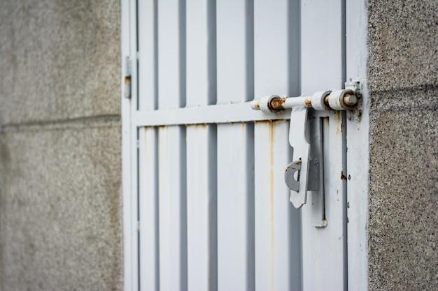金属製の灰色のドアにさびたロックのクローズアップショット