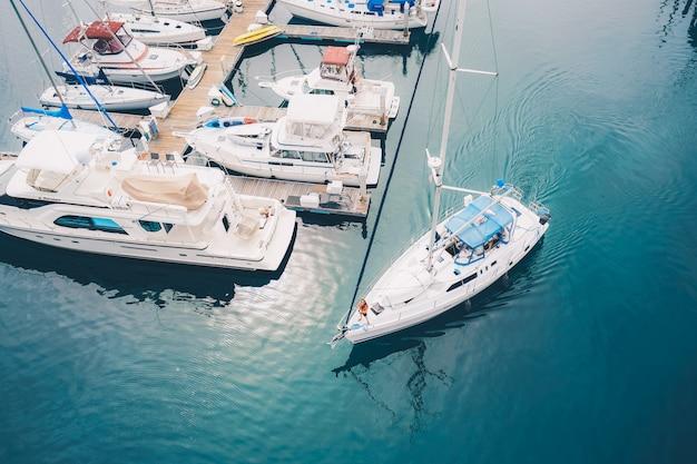 マリーナを去る白いボートは水にセーリングをドックします。