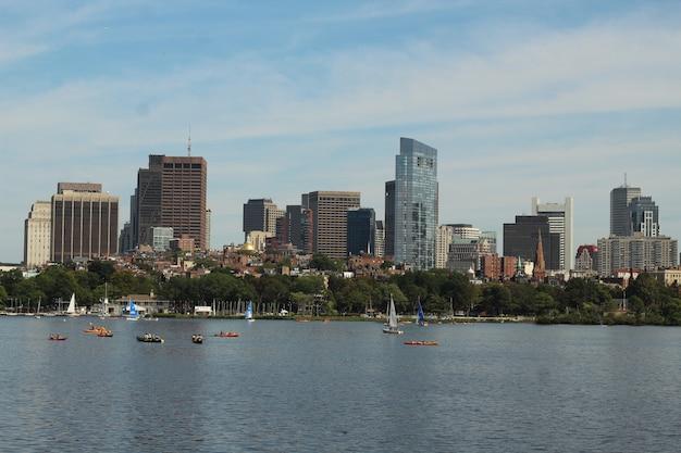 晴れた日に大都市の近くの水でセーリングするボートのスカイライン写真
