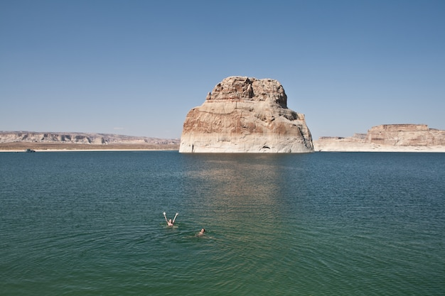 Люди плавают в воде возле большой скалы с ясным небом