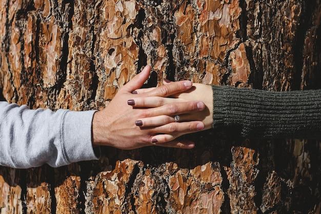 ダイヤの指輪を持つ女性の手と男性の手をつなぐ男性