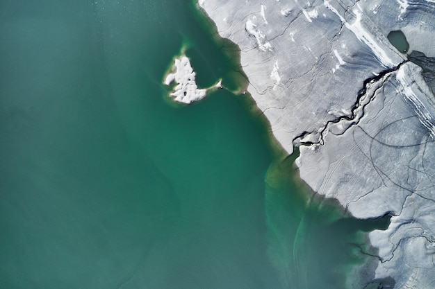 青緑色の水の横にある石の多い海岸に大きな亀裂のハイアングルショット