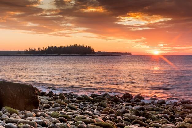 Красивый снимок каменистого берега моря и заходящего солнца на заднем плане