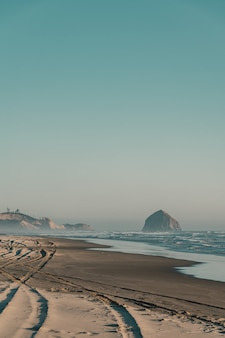 Красивый снимок песчаного пляжа с удивительными волнами в солнечный день