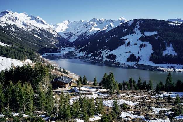 Высокий угол выстрела гор и реки с изолированным домом в лесу на берегу