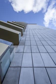 美しい青い空の下でガラスバルコニー付きの高層ビルの垂直ローアングルショット
