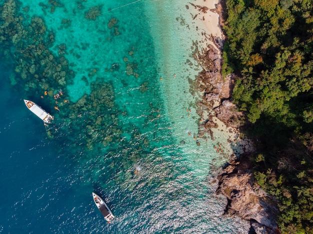 昼間に木で覆われた海岸近くの水にセーリングボートの空中ショット