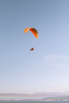 美しい青い空の下をパラシュートで下る孤独な人の垂直方向のショット