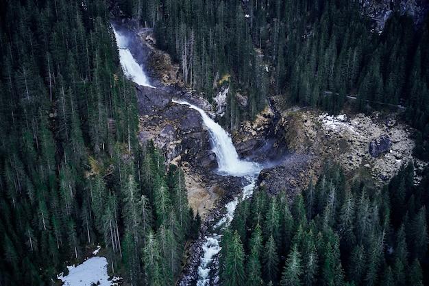 背の高いトウヒの森に囲まれた岩の上の滝の息をのむようなハイアングルショット