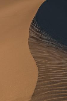 トレイルを残してビーチの砂に到達する水の垂直方向の抽象的なショット