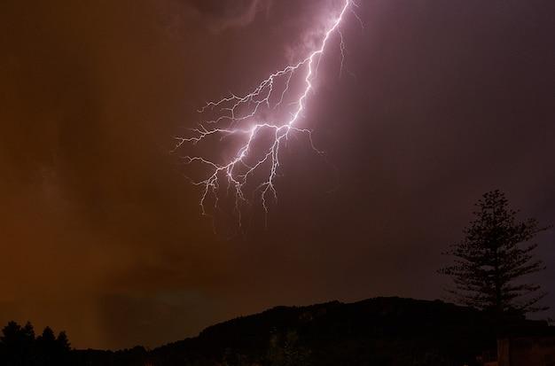 Молния в ночном небе и горы с деревьями