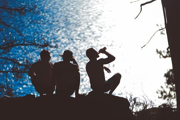 Горизонтальный силуэт трех друзей, болтающихся около моря и пьющих пиво вечером