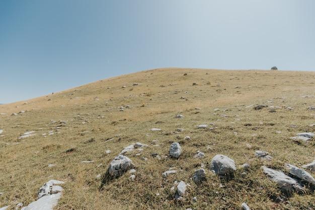 美しく青い空の下に岩がたくさんある山と丘