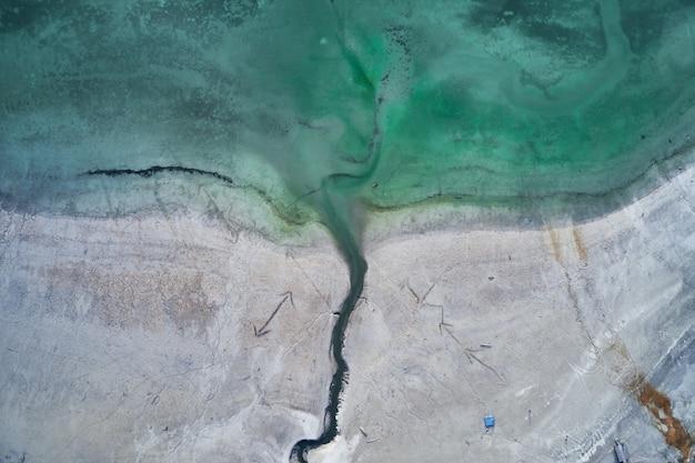矢印の刻印がある海岸の横にある海の青緑色の水のハイアングルショット