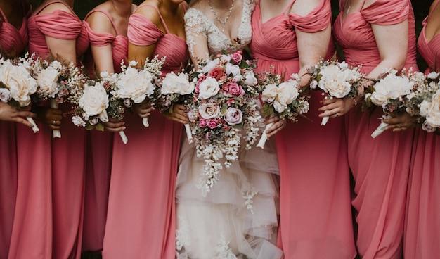 花を持って彼女のブライドメイドと花嫁のショットを閉じる