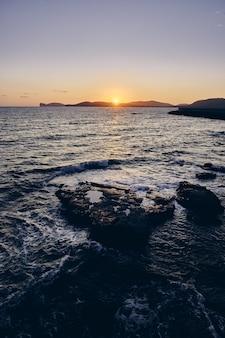 遠くの山の後ろに太陽が輝いている海の岩の垂直方向のショット