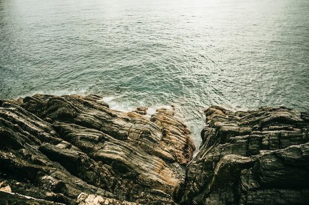 日中の海の近くの美しい岩のハイアングルショット