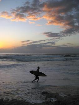 日没時に波状の海の近くを歩いてサーフボードを保持している人の垂直ショット
