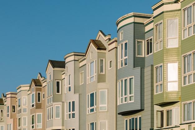 澄んだ空とお互いの近くの異なる色のアパート