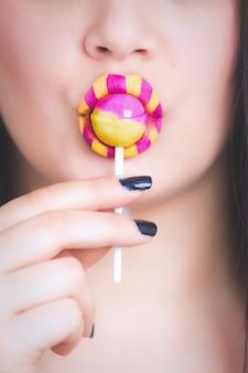 ロリポップを食べる黄色とピンクの口紅を持つ女性の垂直のクローズアップショット