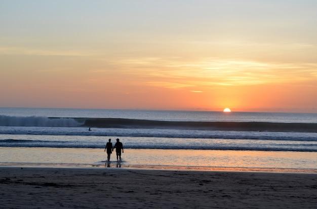 Силуэт пары гуляя в воду около берега с красивейшим небом