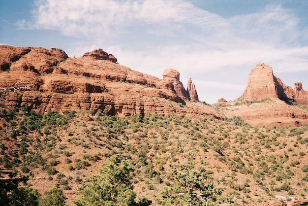 Красивые пейзажи скалистых каньонов в окружении кустов под захватывающим облачным небом