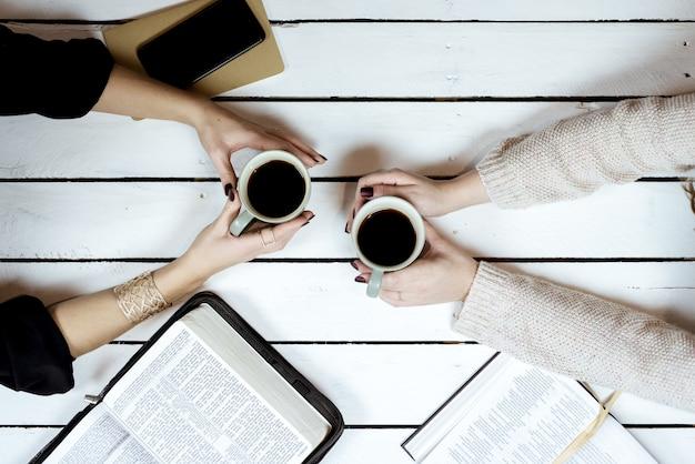 開いた本の近くにコーヒーを保持している女性のオーバーヘッドショット