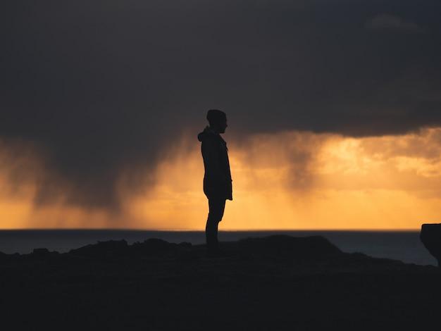 Мужчина стоя на скале с желтым и облачным небом на заднем плане